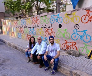 The Chain Effect members Zeina and Hadrien sit by a completed mural with a local man who helped with the painting in Ain el Mreisseh, 2016.