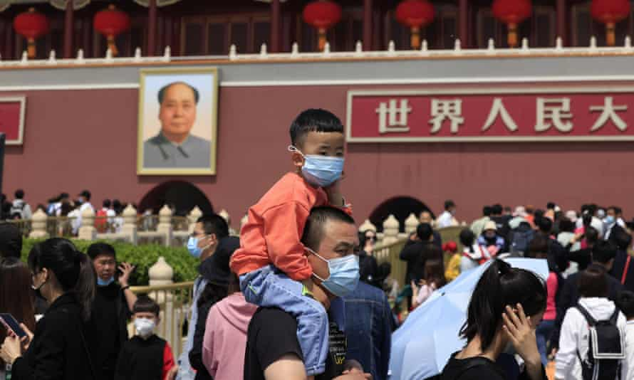 A man and child visit Tiananmen Gate near a portrait of Mao Zedong in Beijing