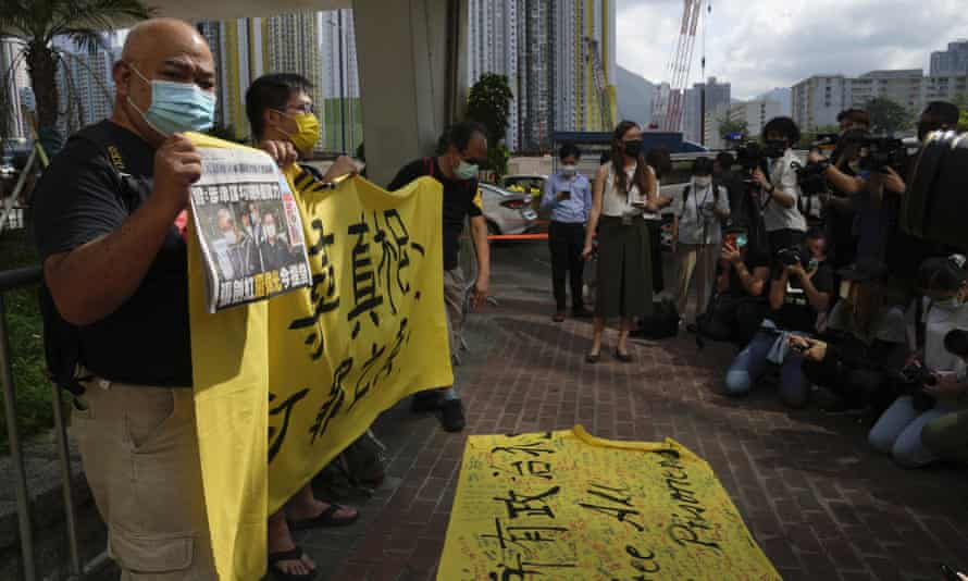 Pro-democracy activists holding a copy of Apple Daily newspaper and banner protest outside court in Hong Kong on Saturday.