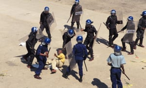 Zimbabwean riot police surround a protester