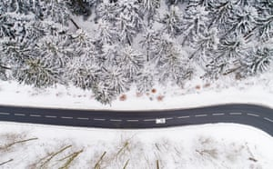Winter In Lower Saxony, Germany. A car drives down a street bordering on a forest doused in powdery snow.