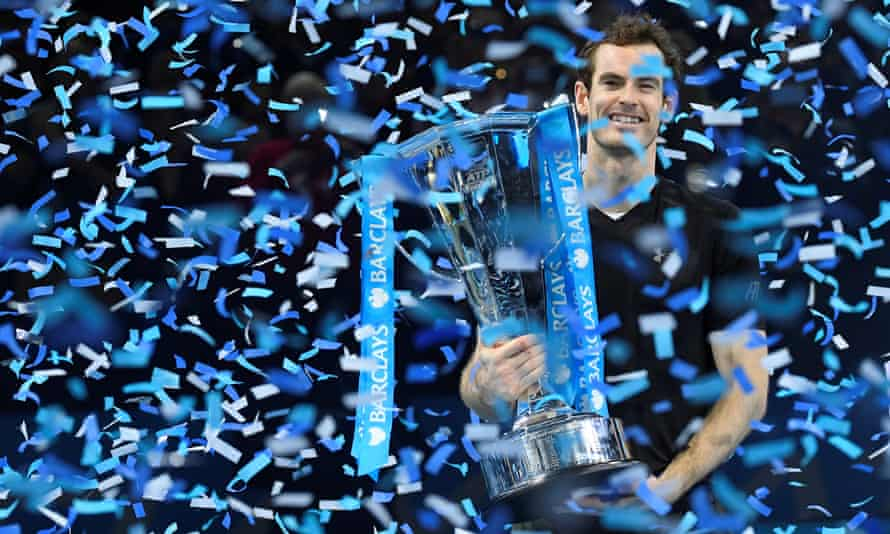 Andy Murray holding a trophy, amid a shower of  blue and white confetti.