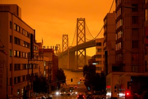 The San Francisco Bay Bridge is seen under an orange smoke-filled sky.