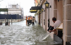 A man empties a bucket of water on a flooded street during a high-water (Acqua Alta) alert in Venice.