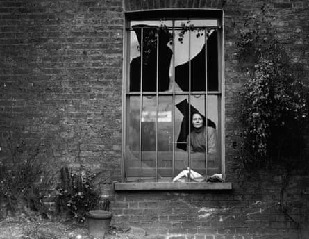 19th December 1913: A woman peers through a shattered window in Holloway prison after an explosion by suffragettes who had tried to blow the place up.