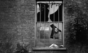 A woman peers through a shattered window at Holloway prison