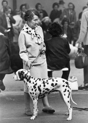 A woman wears a spotty scarf next to a dalmatian