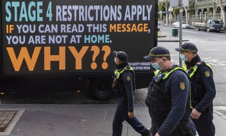 masked police walk past a lockdown sign