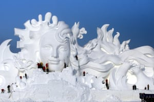 Artists work on snow sculptures at an exhibition in Harbin