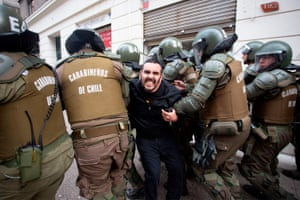 Riot police detain a demonstrator in Santiago, Chile