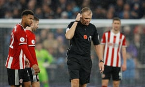 Graham Scott receives the VAR decision to disallow a goal scored by Sheffield United's David McGoldrick against Tottenham on Saturday.