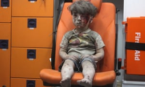 Slaughter of the innocents: wounded Syrian child Omran Daqneesh sits alone in the back of the ambulance after being rescued following an air strike.