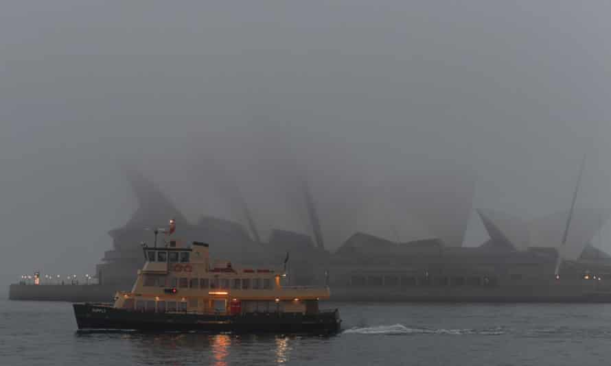 A ferry goes past the Sydney Opera House, shrouded in fog