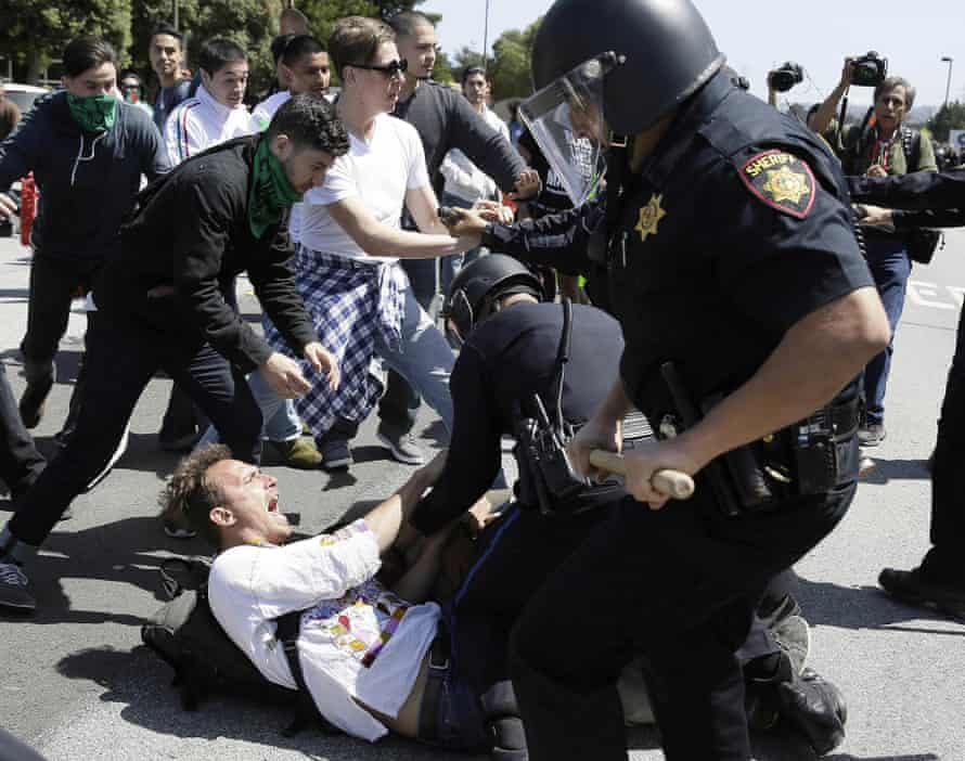 Police officers take a man into custody who was protesting Donald Trump outside the California GOP convention.