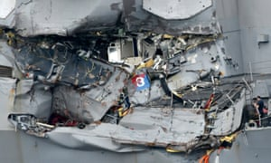 A sailor looks at the damaged area of the USS Fitzgerald at Yokosuka naval base.
