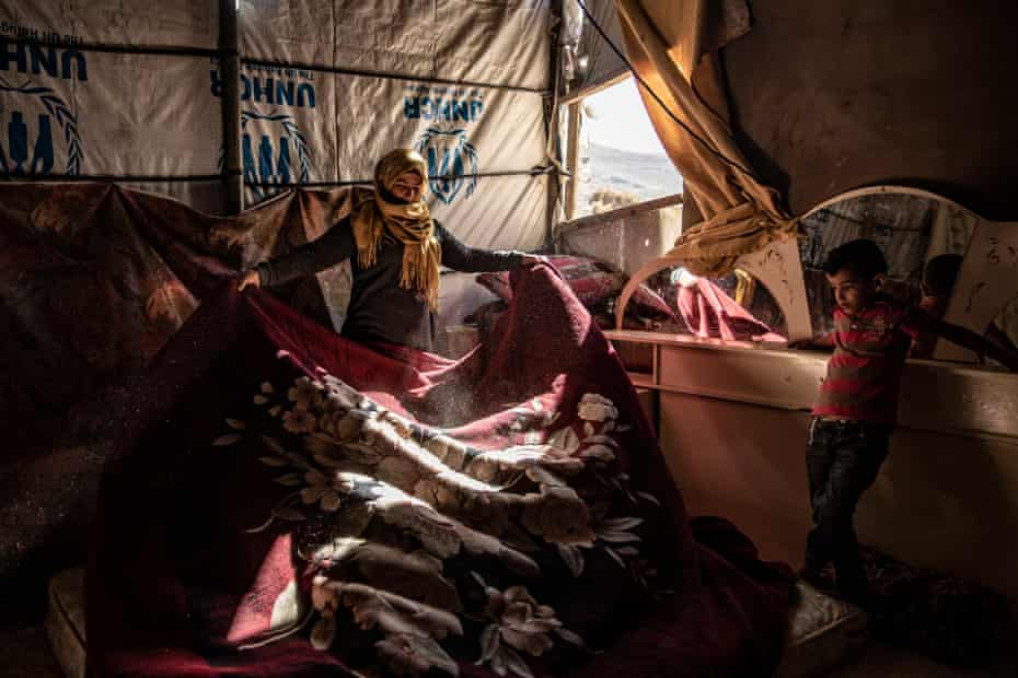 Nisrine, 27, cleans the small room where she lives with her husband and four children