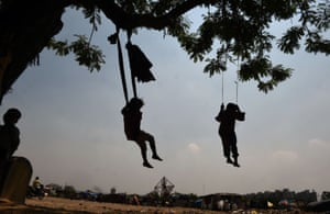 Children play on makeshift swings suspended from a tree on the outskirts of New Delhi.