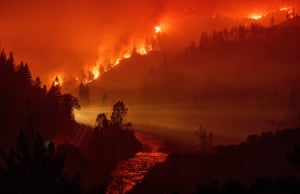 Light from a train is seen as it rounds a bend near the Sacramento river as the Delta Fire engulfs a valley.