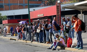 Workers wait for the bus to return to their homes on Thursday in Caracas.