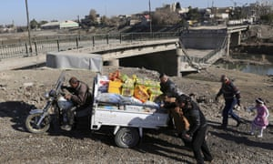 Men push a motorcycle cart loaded with possessions next to a collapsed river bridge in Mosul
