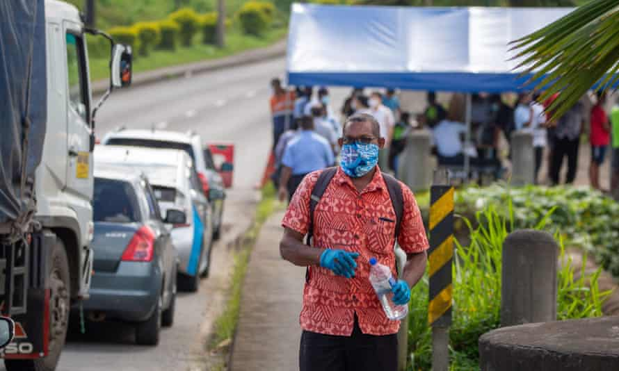 Security officers check cars along a road in Suva after the Fijian capital entered a 14-day lockdown after a leak from a quarantine facility and a funeral caused Covid-19 to spread in the community.