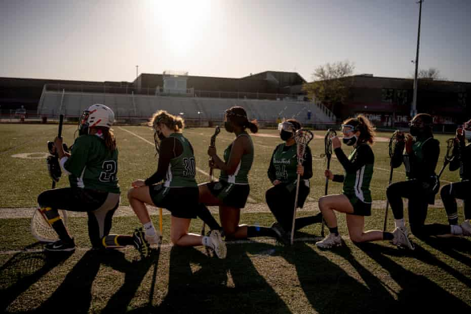 The Cass Technical High School Girl's lacrosse team kneels for the National Anthem before the game against Chippewa Valley in Clinton Township, Michigan on April 30, 2021. Cass Tech took their second win of the season 14-6.
