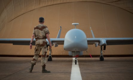 A French soldier of the Serval operation in Mali stands in front of a Harfang drone at the French army base in Niamey.