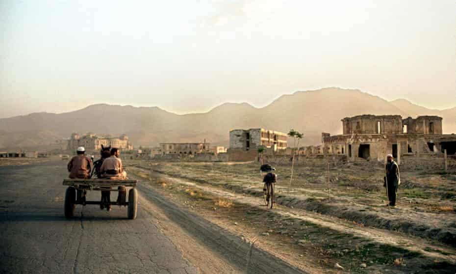 Two men on a horse carriage ride through a desolate area in the south of the Afghan capital Kabul