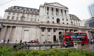 A red bus drives past the Bank of England on Threadneedle Street