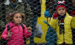 Children line up as they walk along a border fence after they crossed the Slovenian-Austrian border, near the village of Spielfeld, Austria, on 16 February.