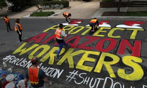 Activists paint a protest message on the street outside one of Jeff Bezos's homes in Washington.
