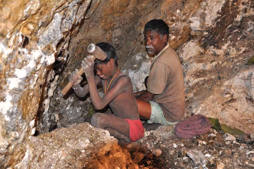In this photograph from 2013, seven-year-old Karulal works with his father in a mica mine.