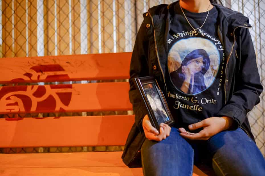 Rosenda Ortiz, sitting at the bus stop where the murder victims used to hang out, wearing a T-shirt commemorating her sister, Janelle Ortiz.