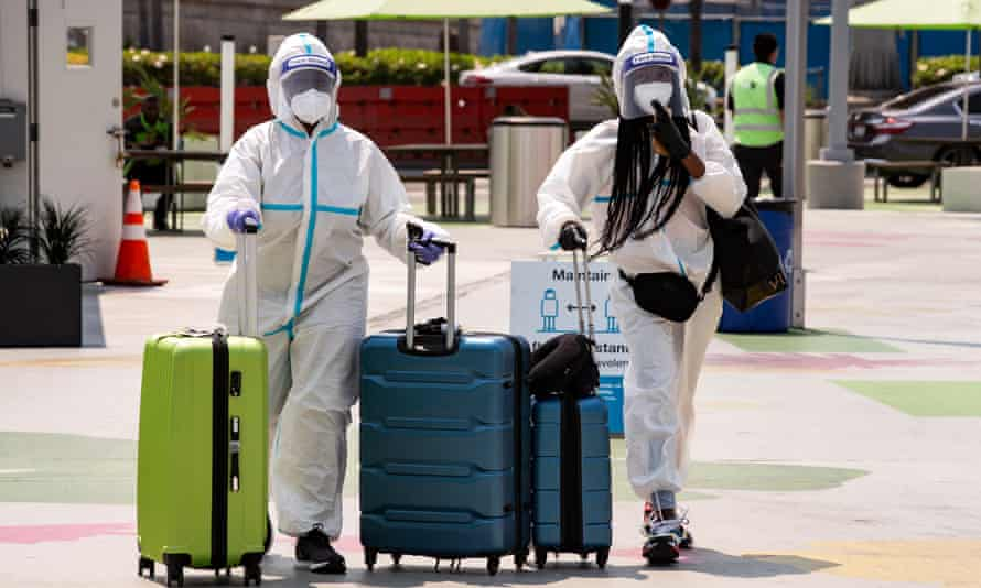 Two passengers in full protective gear push their luggage as they arrive in the rideshare zone of the LAX airport to catch a ride in Los Angeles, California.
