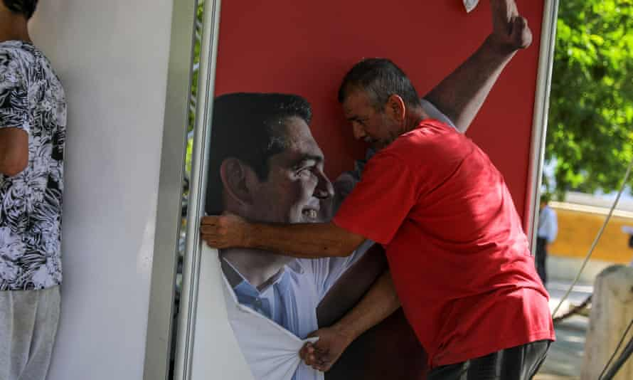 A worker removes a poster of outgoing Greek prime minister Alexis Tsipras.