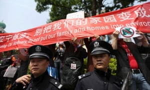 Police officers stand guard as residents raise a banner to protest against a planned refinery in Kunming, Yunnan province. China has introduced measures to empower citizens to use the law as a tool to protect the environment, Thornton says.