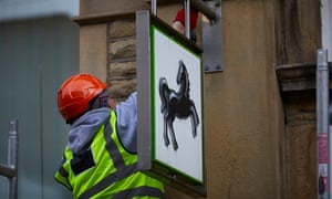 A workman dismantles a Lloyds sign from a closed branch in Hebden Bridge, Yorkshire.