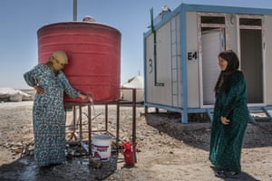 Two women fill buckets at a water store in the camp