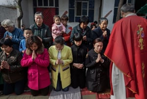 Catholics wait to take communion during the Palm Sunday mass at a 'house church' near Shijiazhuang.