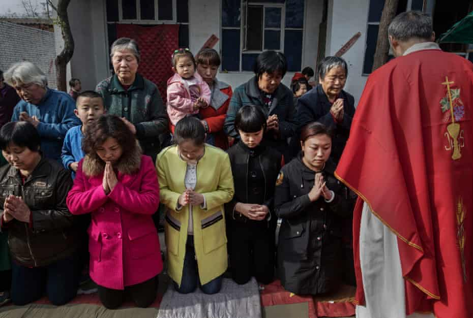 Catholics wait to take communion during the Palm Sunday mass at a 'house church' near Shijiazhuang.