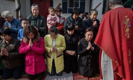 Chinese Catholic worshippers wait to take communion
