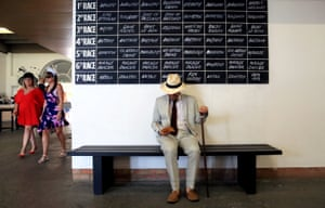 A racegoer studies his card on day four of 'Glorious Goodwood' in Chichester, UK