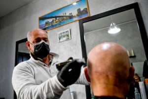 A barber wears a protective mask on his face and gloves on his hands at work in Naples