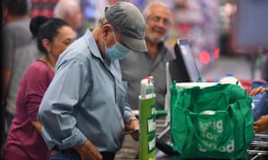 A man wears a face mask at a checkout in a Woolworths supermarket in Melbourne on Thursday as the supermarket allows the elderly and people with disabilities access to early morning shopping.