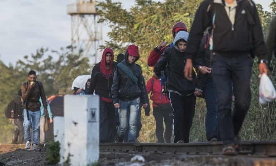 Migrants and refugees who arrived from Serbia walk on the track of the Horgos, Serbia, and Szeged, Hungary, railway line near the border village of Roszke, 180 kms southeast of Budapest, Hungary, during sunrise Wednesday, Sept. 9, 2015. (Sandor Ujvari/MTI via AP)