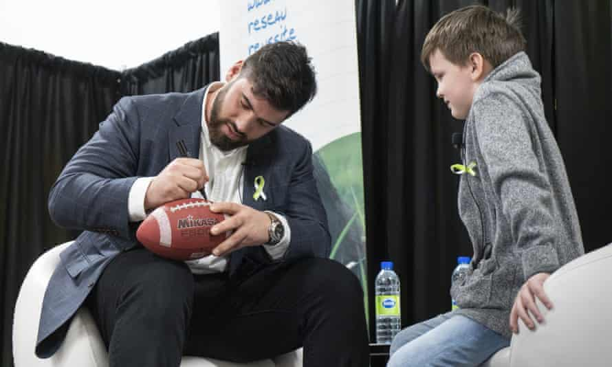 Laurent Duvernay-Tardif signs a football for a young fan in his hometown of Montreal