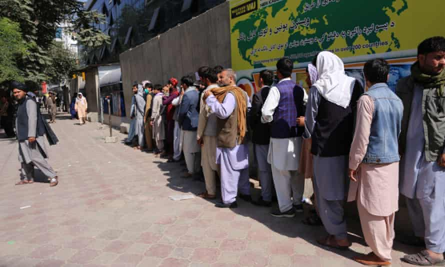 People queue outside a bank to withdraw cash on Thursday after the Taliban's takeover of Kabul