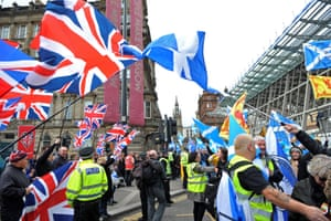 Pro-Scottish independence activists wave Saltire flags as they pass pro-Union demonstrators flying Union flags
