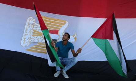 A man holds Palestinian flags in front of an Egyptian flag in the Gaza Strip