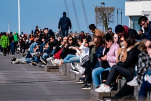 People sit in the sun at the western harbour in Malmo, Sweden, on 5 April.